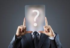 Homem de negócio novo que guardara sinais do ponto de interrogação Fotografia de Stock Royalty Free