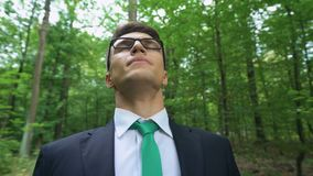 Homem de negócio novo que respira profundamente na floresta verde, apreciando o ar fresco limpo filme