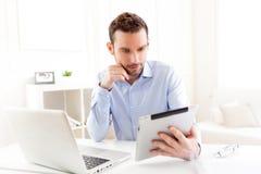 Homem de negócio novo que trabalha em casa em sua tabuleta Imagens de Stock