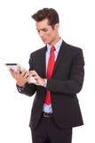 Homem de negócio novo que trabalha em sua almofada da tabuleta fotografia de stock royalty free