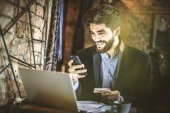 Homem de negócio novo que usa o telefone esperto às faturas pagamento em linha fotografia de stock