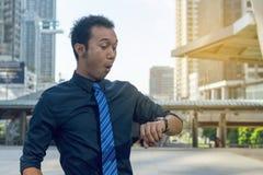 Homem de negócio novo que verifica o tempo imagens de stock royalty free