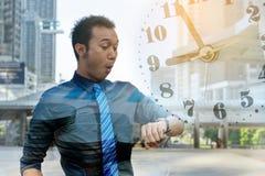 Homem de negócio novo que verifica o tempo imagem de stock