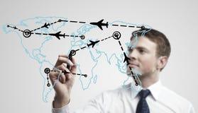 Homem de negócio novo rotas desenhando de um avião Fotografia de Stock