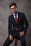Homem de negócio novo sério que senta-se em um tamborete Imagens de Stock Royalty Free