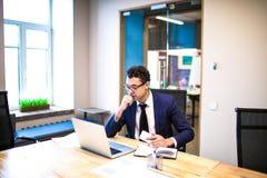 Homem de negócio pensativo na apresentação de observação do terno no laptop, sentando-se no interior do escritório fotografia de stock
