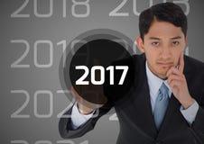 Homem de negócio pensativo no fundo digitalmente gerado que toca em 2017 Fotografia de Stock