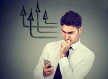 Homem de negócio pensativo que usa o telefone celular que texting enviando mensagens fotografia de stock royalty free