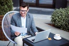 Homem de negócio positivo que senta-se na tabela Foto de Stock Royalty Free