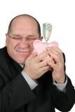 Homem de negócio que abraça o banco Piggy Imagens de Stock Royalty Free