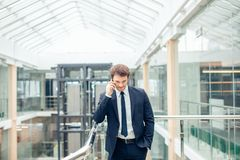 Homem de negócio que anda ao falar no telefone celular em sua maneira de trabalhar foto de stock