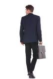 Homem de negócio que anda ao guardar sua pasta Fotografia de Stock