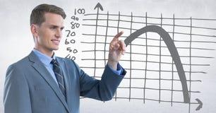 Homem de negócio que aponta contra o gráfico cinzento e o fundo branco Imagens de Stock