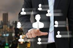 Homem de negócio que aponta o ícone dos povos de recursos humanos Foto de Stock Royalty Free