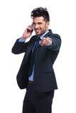 Homem de negócio que aponta o dedo ao falar no smartphone imagem de stock royalty free
