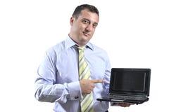 Homem de negócio que aponta a um portátil Fotografia de Stock Royalty Free