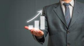 Homem de negócio que apresenta o gráfico crescente Fotografia de Stock