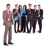 Homem de negócio que apresenta sua equipe feliz bem sucedida Foto de Stock Royalty Free