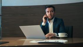 Homem de negócio que chama pelo telefone celular ao trabalhar no caderno no escritório vídeos de arquivo