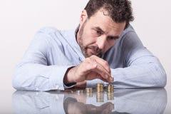 Homem de negócio que conta o dinheiro, pilhas de moedas Fotografia de Stock Royalty Free