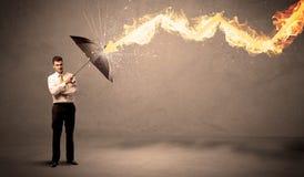 Homem de negócio que defende-se de uma seta do fogo com um umbrell Fotografia de Stock