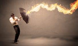 Homem de negócio que defende-se de uma seta do fogo com um umbrell Imagem de Stock Royalty Free