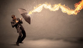 Homem de negócio que defende-se de uma seta do fogo com um umbrell Imagens de Stock