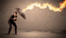 Homem de negócio que defende-se de uma seta do fogo com um umbrell Imagem de Stock