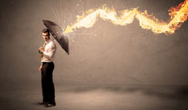Homem de negócio que defende-se de uma seta do fogo com um umbrell Foto de Stock