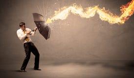 Homem de negócio que defende-se de uma seta do fogo com um umbrell Foto de Stock Royalty Free