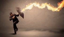 Homem de negócio que defende-se de uma seta do fogo com um umbrell Fotos de Stock
