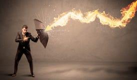 Homem de negócio que defende-se de uma seta do fogo com um umbrell Imagens de Stock Royalty Free