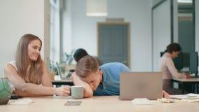 Homem de negócio que dorme em coworking O profissional dá o café ao colega cansado vídeos de arquivo