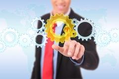 Homem de negócio que empurra um botão da roda denteada Fotos de Stock Royalty Free