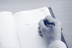 Homem de negócio que escreve uma nota em seu local de trabalho Fotografia de Stock Royalty Free