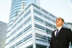 Homem de negócio que está pelo edifício moderno foto de stock
