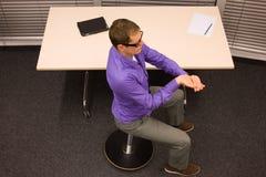 homem de negócio que exercita na mesa no local de trabalho Imagem de Stock
