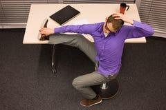 homem de negócio que exercita na mesa no local de trabalho Fotografia de Stock Royalty Free