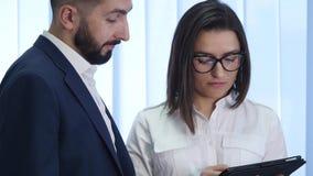 Homem de negócio que explica algo a uma mulher com uma tabuleta digital em um escritório filme