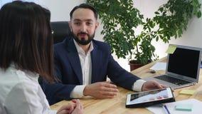 Homem de negócio que explica algo a uma mulher com uma tabuleta digital em um escritório video estoque