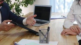 Homem de negócio que explica algo a uma mulher com uma tabuleta digital em um escritório vídeos de arquivo