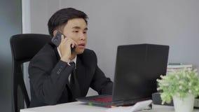 Homem de negócio que fala no telefone celular e que usa o portátil filme