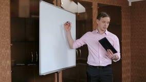 Homem de negócio que faz uma apresentação na frente do whiteboard
