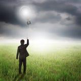 Homem de negócio que guarda o balão do bulbo nos campos e no raincloud foto de stock
