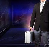 Homem de negócio que guarda o breifcase forte do metal que está contra o ind Imagem de Stock Royalty Free