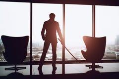 Homem de negócio que guarda o katana no escritório Fotografia de Stock Royalty Free