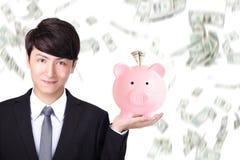 Homem de negócio que guarda o mealheiro cor-de-rosa Fotografia de Stock