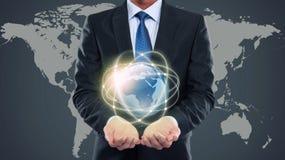 Homem de negócio que guarda o mundo pequeno dos multimédios Imagens de Stock