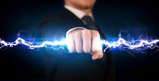 Homem de negócio que guarda o parafuso leve da eletricidade em suas mãos Imagens de Stock Royalty Free