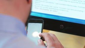 Homem de negócio que guarda o telefone esperto e que lê o computador dianteiro do email no escritório video estoque
